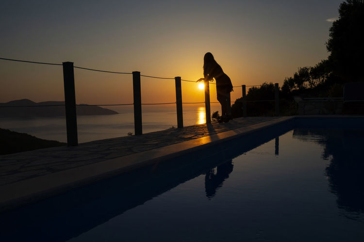 Silhouette person by swimming pool against sky during sunset