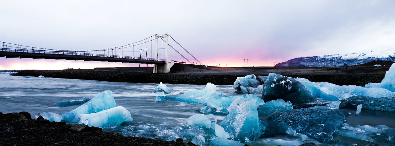 Suspension Bridge Over Sea Against Cloudy Sky During Winter At Sunset