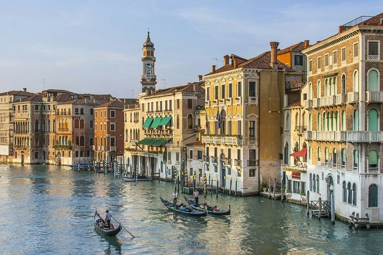 Gondolas on grand canal by buildings in city