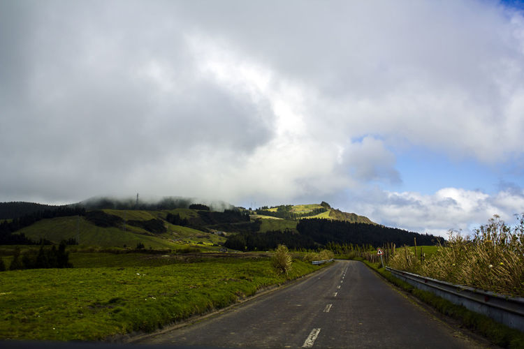 Rural road leading through green hills Asphalt Azores Country Field Grass Green Color Rolling Landscape Rural Scenic Travel Trip Cloud - Sky Country Road Direction Environment Green Island Hill Landscape Nature No People Non-urban Scene Outdoors Remote Road Road Trip