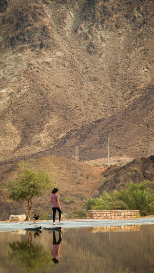 A young female teenager walking with a small dog in the mountains beside a clear mirror lake in Hatta, United Arab Emirates One Person Water Full Length Day Nature Mountain Outdoors Adult Real People Lifestyles Plant Scenics - Nature Beauty In Nature Lake Side View Land Leisure Activity Standing Tranquility Exercise Walking Dog Reflection Early Morning Scenery