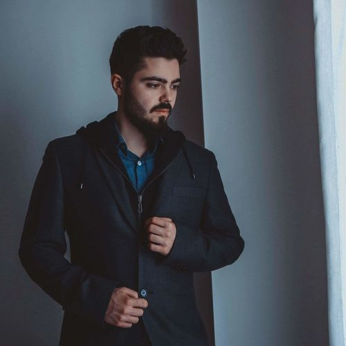 Thoughtful Young Man Wearing Coat Standing Against Wall