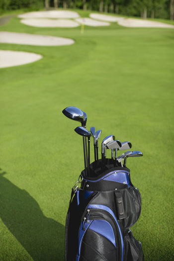 Golf clubs in bag on sunny golf course