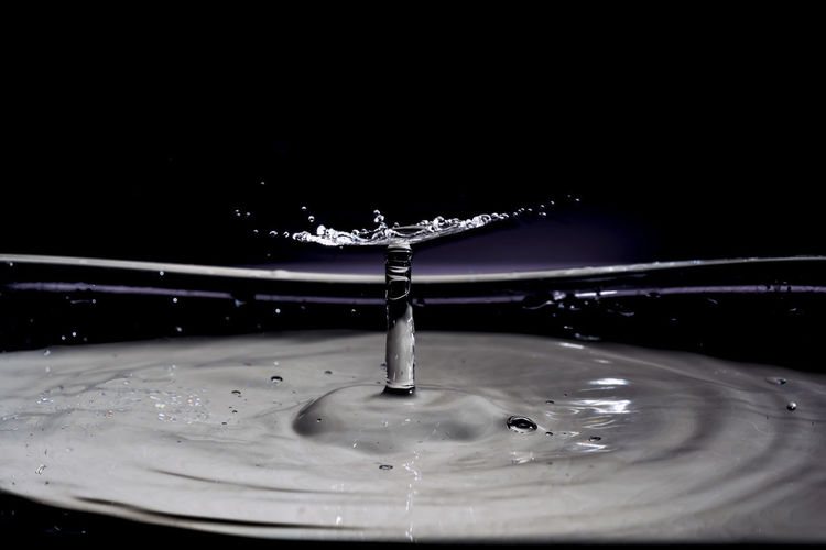 Close-up of drop splashing on water against black background