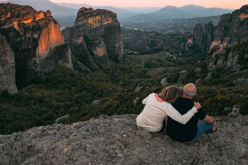 Rear view of couple sitting on rock