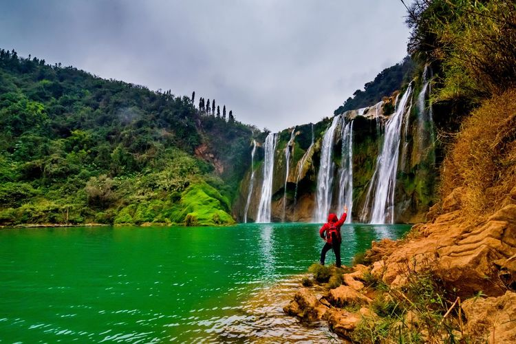 Jiulong waterfall yunnan, china. Freedom Hiking Jiulong Waterfall Man Tourist Adult Adults Only Adventure Beauty In Nature Day Full Length Hand Raised Journey Leisure Activity Men Motion Mountain Nature One Man Only One Person Only Men Outdoors People Real People Rock - Object Scenics Sky Success Tourism Traveler Tree Water Waterfall Young Adult Yunnan