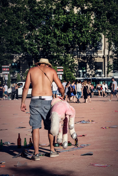 Drunk Gay Pride Alcohol Building Exterior Built Structure Day Large Group Of People Leisure Activity Lifestyles Mammal Men Outdoors People Real People Rear View Shirtless Staggered Stumble Tree