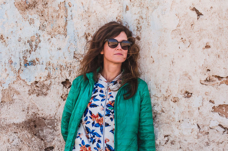 Woman Wearing Sunglasses And Jacket Standing Against Weathered Wall