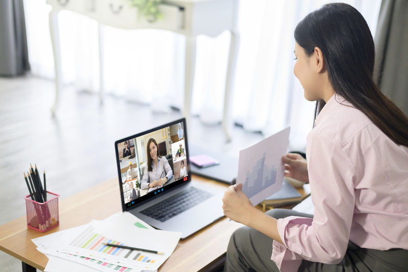 Smiling businesswoman video conferencing in office