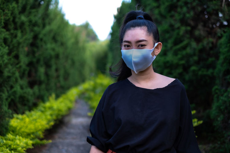 Young asia woman standing and put on a face mask