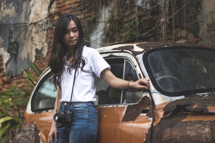 Young woman smiling while standing by abandoned car