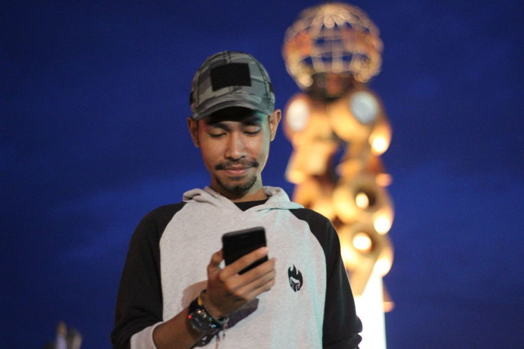 Portrait of young man using smart phone against sky