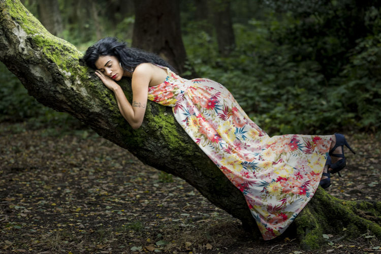 Young woman lying down on tree trunk in forest
