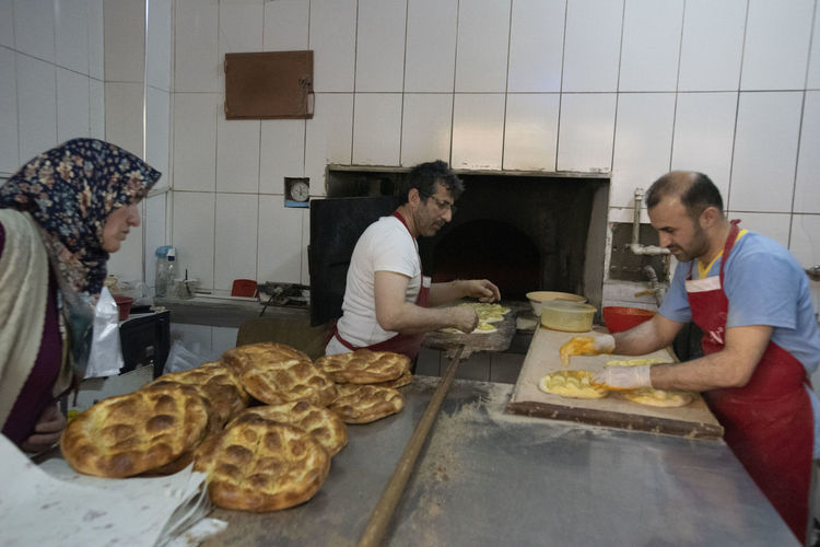 Food And Drink Food Adult Women Indoors  Preparation  Group Of People Lifestyles Men Waist Up Domestic Room People Togetherness Bread Young Adult Standing Young Men Sitting Kitchen Table Preparing Food Pide Ramazan Gölyazı