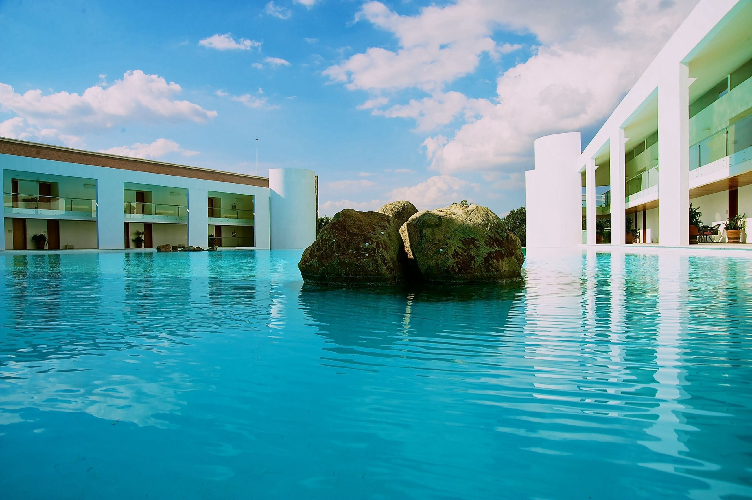 water, architecture, building exterior, built structure, sky, waterfront, reflection, cloud - sky, swimming pool, blue, cloud, house, building, rippled, residential building, residential structure, day, window, outdoors, nature