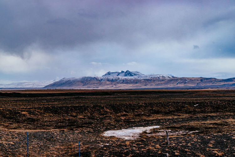 Scenic view of wide barren field against remote mountain in winter