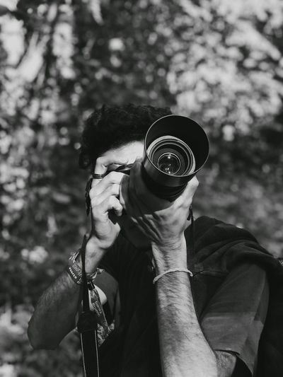 Man photographing against trees