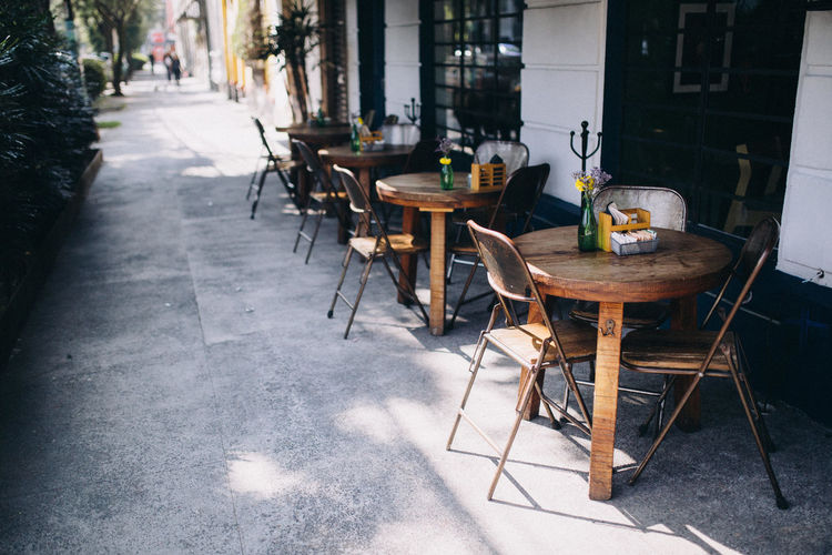 Empty chairs and tables at sidewalk cafe in mexico city, mexico
