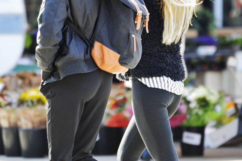 Midsection of man and woman walking outdoors