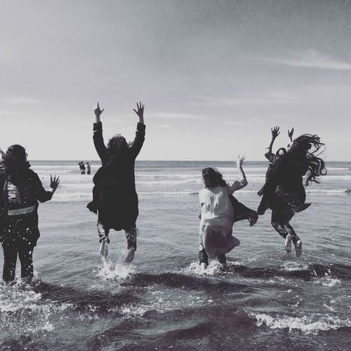 Rear view of female friends jumping in sea against sky