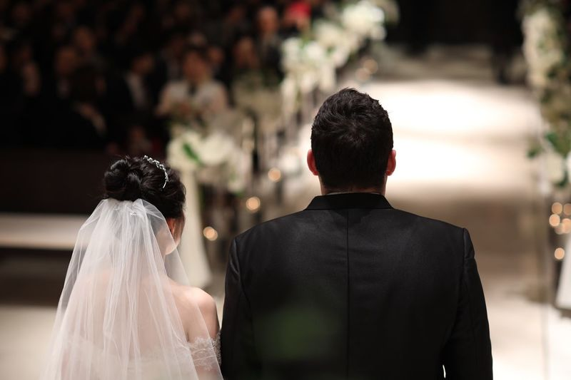 Rear view of wedding couple standing in church