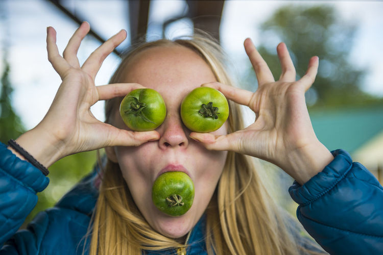 Young woman playing with green tomato