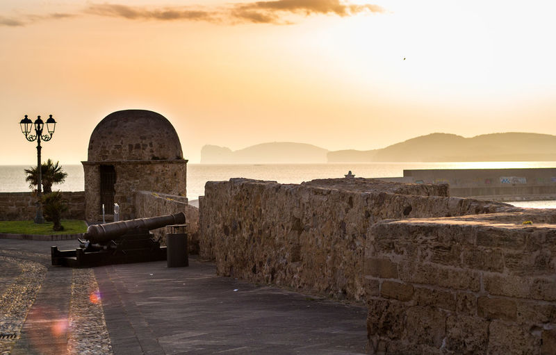 View from Alghero bastion Alghero Bastion Bastione Cannon Sunset Travel Tourism Sardinia Sardegna Seascape Stones City Sunset Grave Arch Sky Architecture Historic Civilization History Historic Building The Past Ancient Ancient Civilization Old Ruin Ancient History Orange Color Sun Archaeology Ruined