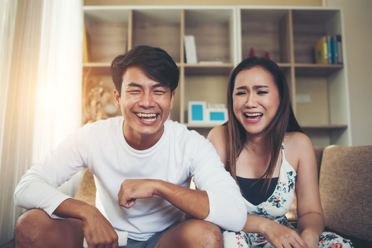 Two People Togetherness Young Adult Happiness Sitting Lifestyles Casual Clothing Emotion Young Men Real People Young Women Front View Indoors  Furniture Leisure Activity Smiling Women Sofa Adult People Couple - Relationship Positive Emotion