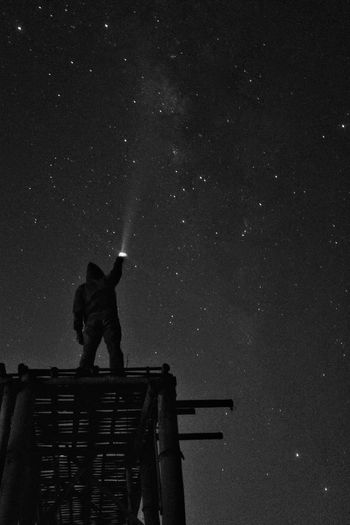 Low angle view of silhouette man holding illuminated flashlight against star field at night