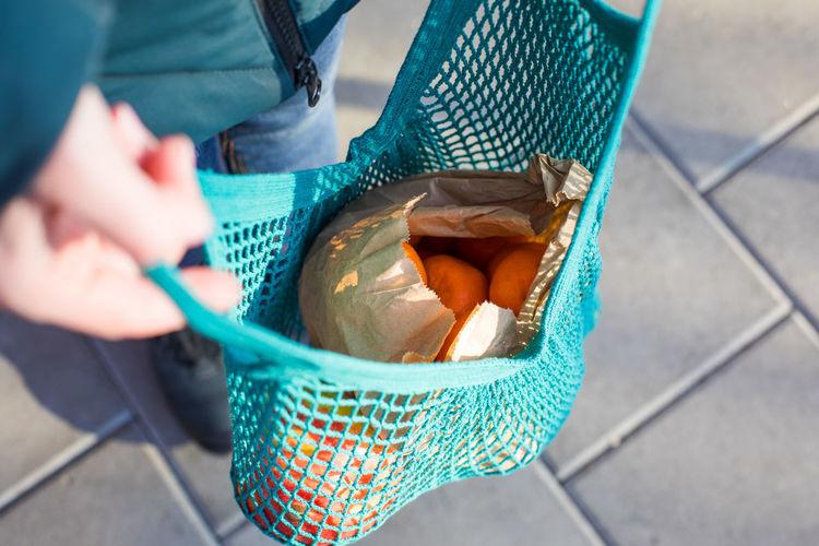 High angle view of hand holding mesh bag