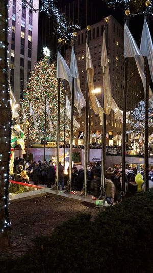 Christmas Around The World Rockefeller Center, New York Christmas Tree Christmas Lights Christmas Decorations Huge Crowds Of People Flags Blowing