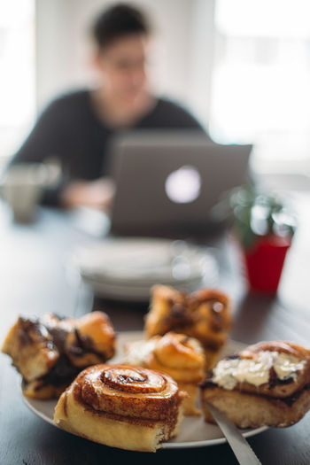 Almost coffee break Man Office Work Cake Cinnamon Bun Close-up Communication Day Dessert Focus On Foreground Food Food And Drink Indoors  Laptop One Person People Plate Ready-to-eat Real People Sweet Food Table Technology Wireless Technology
