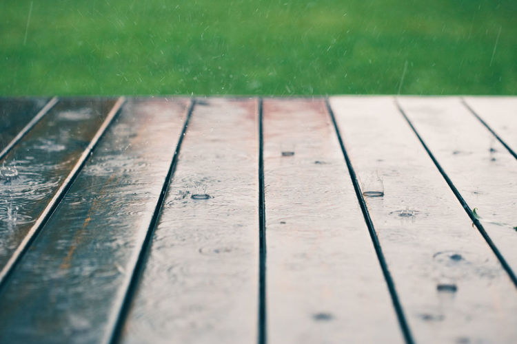 Closeup of wood planks while raining in perspective with grass at the top
