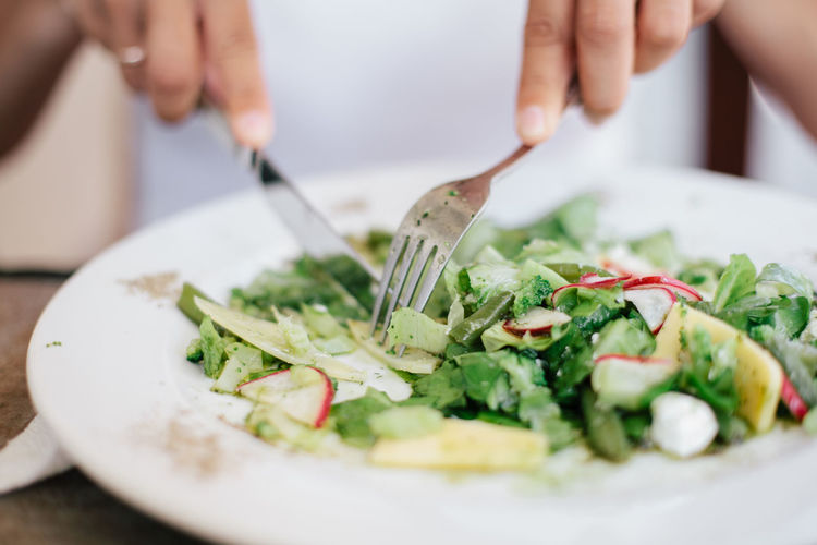 Cropped image of hands eating salad at home