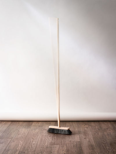 High angle view of broom on floor by wall at home