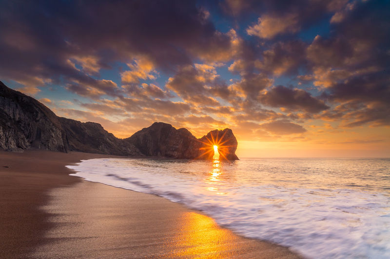 Durdle door sunstar at Sunrise 20mm 6D Beach Beauty In Nature Canon Cloud - Sky Dramatic Sky Drastic Edit Durdle Door Landscape Love Photography Nature No People Outdoors Sand Scenics Sea Sky Sunrise Sunstar Travel Vacations Water Wave Winter Morning