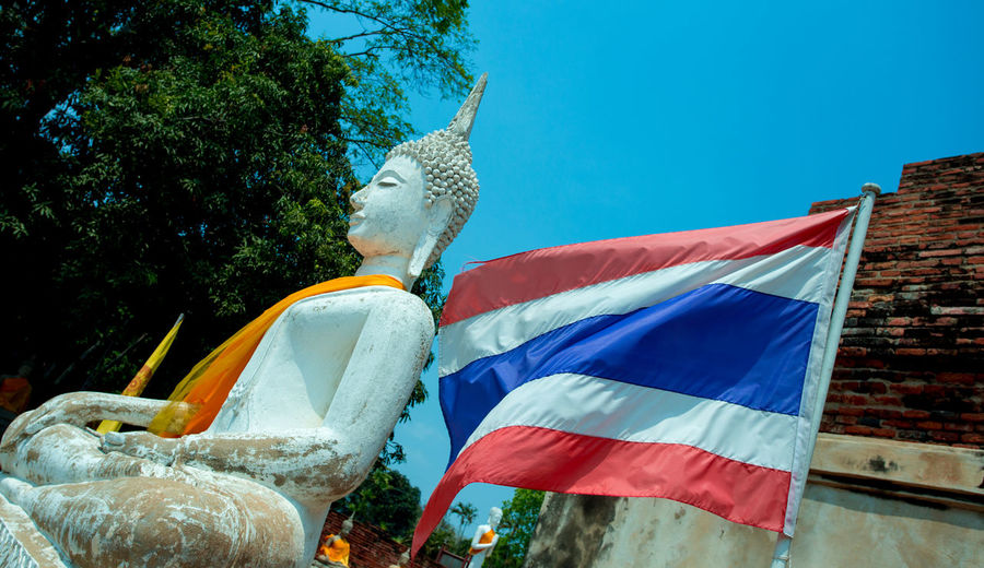 Low Angle View Of Buddha Statue And Thai Flag
