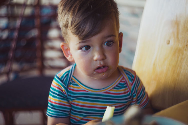 Close-up of boy eating cucumber at home