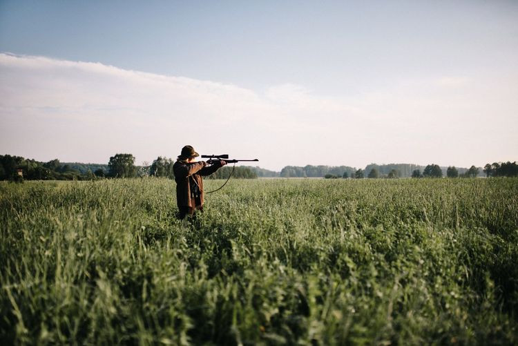 Person Aiming With Gun Amidst Grass On Field