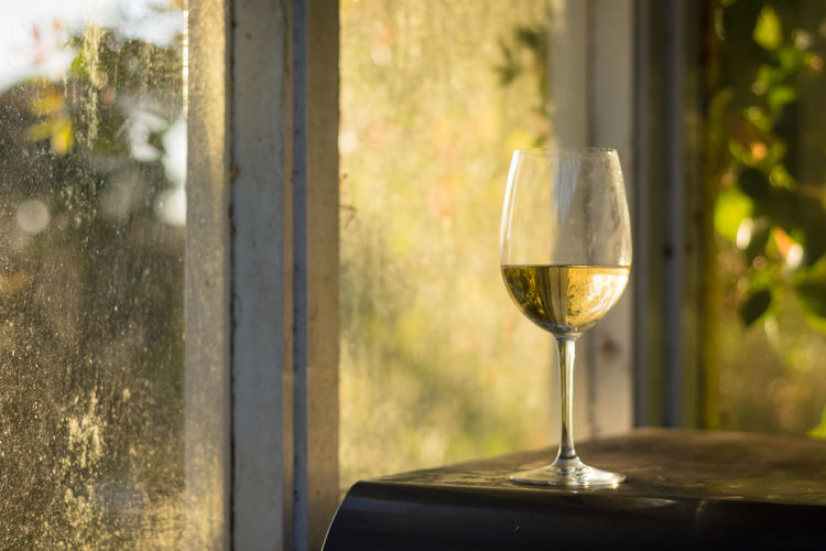 Close-up of wine glass on table against window