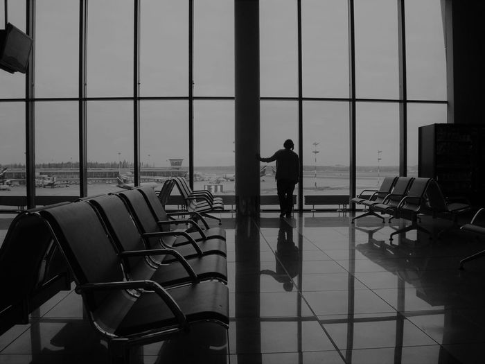 Rear view of man standing by window at airport departure area