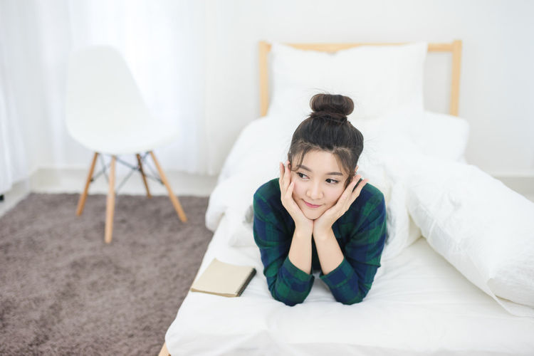 Bed Bedroom Casual Clothing Child Childhood Domestic Room Full Length Furniture Girls Hairstyle Indoors  Innocence Lifestyles Looking At Camera Lying Down Lying On Front One Person Portrait Relaxation Sitting Women