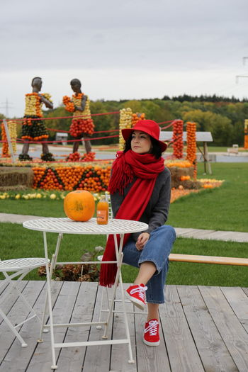 Portrait of young woman with red umbrella against sky during halloween