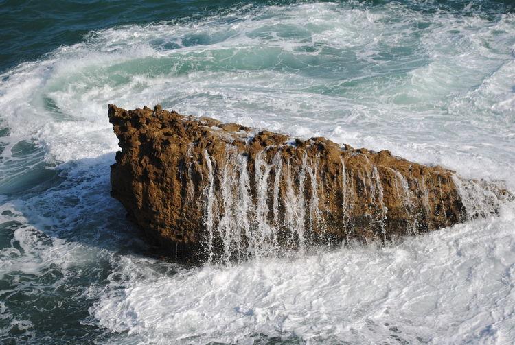 Waves splashing on rock in sea