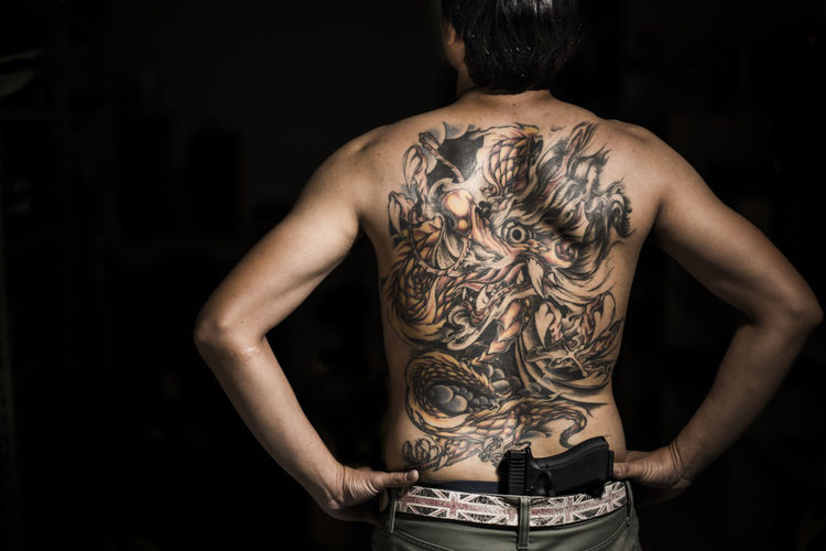 Rear view of tattooed man with gun