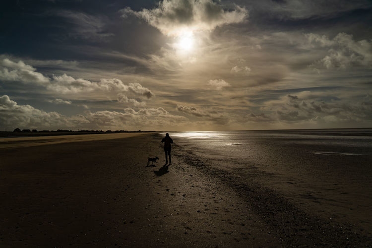 Man walking on beach against sky during sunset