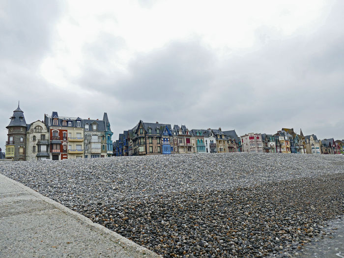 Houses against sky with stones on foreground