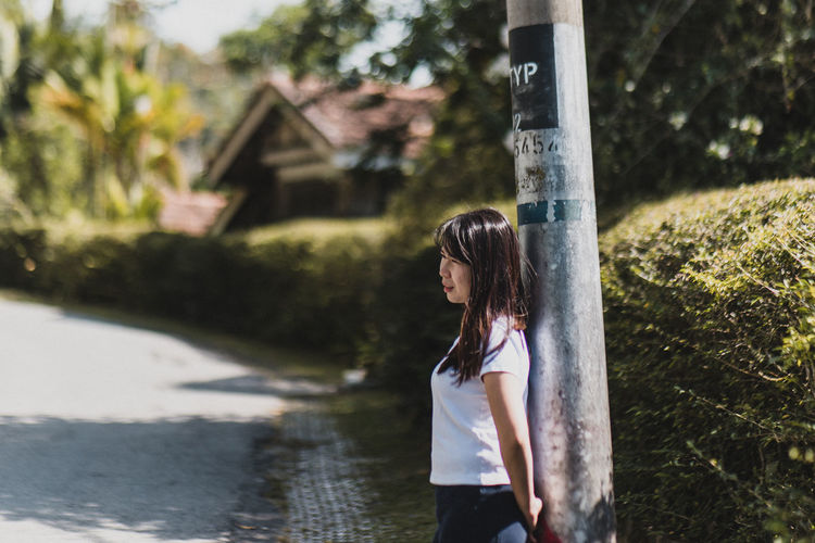 Waiting One Person Real People Tree Casual Clothing Standing Leisure Activity Young Adult Lifestyles Day Side View Young Women Focus On Foreground Women Nature Hairstyle Plant Hair Three Quarter Length Long Hair Outdoors Beautiful Woman