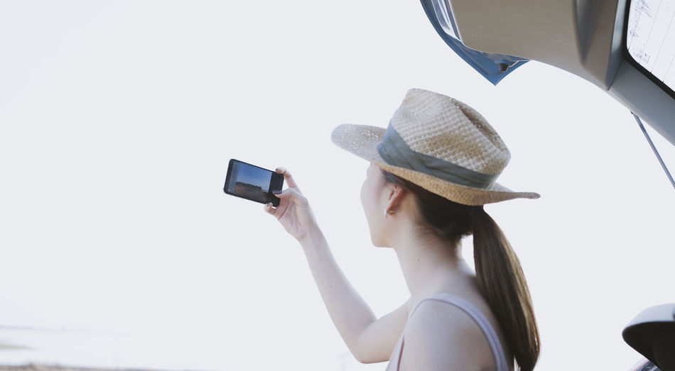 Midsection of woman using mobile phone against clear sky