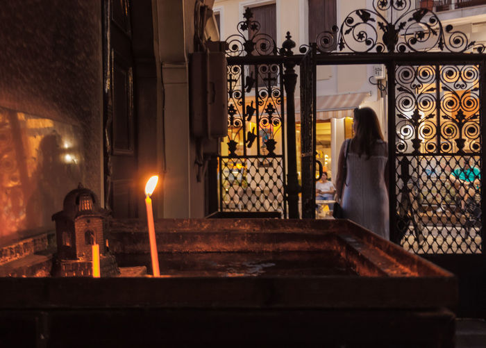 Lit candle on altar in church with woman standing outside gate